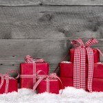 Stack of red Christmas gift boxes with snow on grey wooden backg